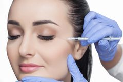 The doctor cosmetologist makes the Rejuvenating facial injections procedure for tightening and smoothing wrinkles on the face skin. Of a beautiful, young woman Stock Photo
