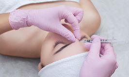 The doctor cosmetologist makes the Rejuvenating facial injections procedure for tightening and smoothing wrinkles on the face skin royalty free stock images