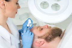 The doctor cosmetologist makes the Rejuvenating facial injections procedure for tightening and smoothing wrinkles on the face skin. Of a men in a beauty salon royalty free stock photography