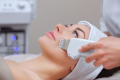 The doctor-cosmetologist makes the ultrasound cleaning procedure of the facial skin of a beautiful, young woman in a beauty salon. stock photos