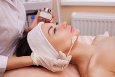 The doctor is a cosmetologist for the procedure of cleansing and moisturizing the skin, applying a mask. With stick to the face of a young woman in beauty salon Stock Images