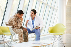 Doctor Counselling Soldier Suffering From Stress. In Hospital Stock Photo