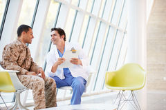 Doctor Counselling Soldier Suffering From Stress. Indoors Stock Image