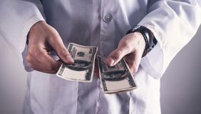 Doctor counting money. Concept of corruption royalty free stock image
