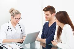 Doctor and couple at desk in clinic Royalty Free Stock Photos