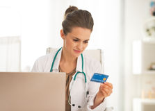 Doctor with credit card making online shopping. Doctor woman with credit card making online shopping Stock Images