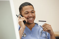 Doctor with credit card on phone Stock Image