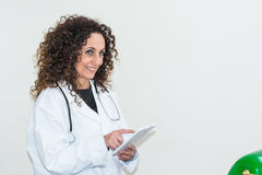 Doctor with curly hair and blacks and with green eyes, use a tab Royalty Free Stock Photos