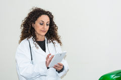 Doctor with curly hair and blacks and with green eyes, use a tab Royalty Free Stock Photo