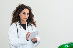 Doctor with curly hair and blacks and with green eyes, use a tab. Let of white color. The new technologies used in the medical field Stock Photography