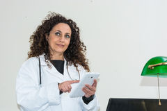 Doctor with curly hair and blacks and with green eyes, use a tab. Let of white color. The new technologies used in the medical field Royalty Free Stock Image