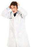 Doctor dado una sacudida eléctrica que lleva a cabo su cabeza con las manos Fotos de archivo libres de regalías