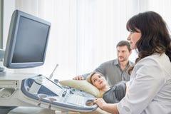 Doctor de asistencia cariñoso de los pares para el procedu del sonido del embarazo ultra foto de archivo libre de regalías