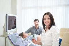 Doctor de asistencia cariñoso de los pares para el procedu del sonido del embarazo ultra foto de archivo