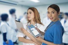 Doctor de dos hembras que sostiene la tableta digital en manos fotos de archivo
