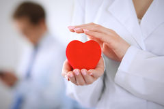 Doctor de Femail que lleva a cabo un corazón rojo en sus manos en un fondo del paciente fotografía de archivo libre de regalías