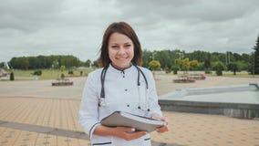 Doctor de la chica joven que camina abajo de la calle con los documentos y la sonrisa Imagenes de archivo