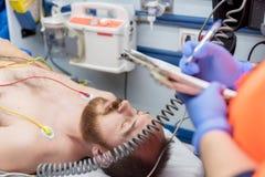 Doctor de la emergencia que llena la lista de la historia paciente en el cojín del tablero en la ambulancia imagenes de archivo