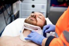Doctor de la emergencia que pone un cuello cervical a un paciente en la ambulancia foto de archivo libre de regalías