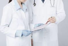 Doctor de la enfermera y del varón que sostiene el cardiograma Foto de archivo libre de regalías