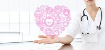 Doctor de la mano con los iconos médicos del corazón Foto de archivo