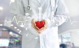 Doctor de la medicina que lleva a cabo forma roja del corazón disponible y el icono médico imagen de archivo libre de regalías