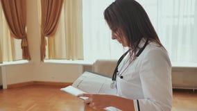 Doctor de la muchacha que camina en hospital con los documentos almacen de video