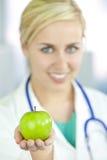 Doctor de la mujer en el hospital que sostiene Apple verde Foto de archivo