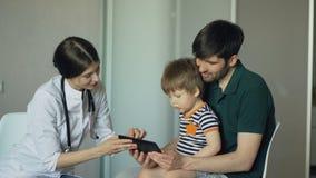 Doctor de la mujer joven que habla con el padre del niño pequeño que usa la tableta en oficina médica metrajes