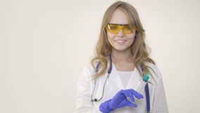Doctor de la mujer joven que sonríe y que sostiene la jeringuilla en el fondo blanco almacen de video