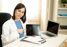 Doctor de la mujer profesional que tiene resultados de la prueba de la demostración de la consulta en el ordenador portátil para  imagenes de archivo