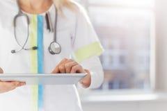 Doctor de la mujer que usa la tableta en hospital Imágenes de archivo libres de regalías