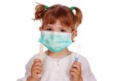 Doctor de la niña en máscara con la jeringuilla Foto de archivo