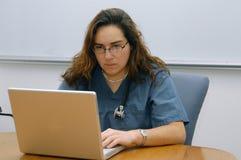 Doctor de la señora que trabaja en el cuaderno Imágenes de archivo libres de regalías