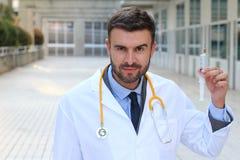 Doctor de mirada sicopático que sostiene una jeringuilla imágenes de archivo libres de regalías