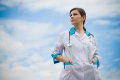 Doctor de sexo femenino acertado en fondo del cielo azul Foto de archivo libre de regalías