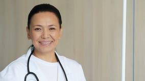 Doctor de sexo femenino alegre que acoge con satisfacción a sus pacientes almacen de metraje de vídeo