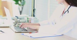Doctor de sexo femenino apuesto usando el cuaderno para el control su historia paciente de la enfermedad en hospital almacen de video