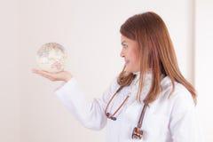 Doctor de sexo femenino asiático que muestra el globo en su mano imagen de archivo libre de regalías