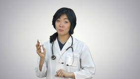 Doctor de sexo femenino asiático que muestra una botella de tabletas, presentando píldoras en el fondo blanco almacen de metraje de vídeo