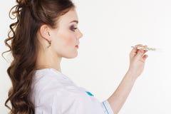 Doctor de sexo femenino bastante joven con el termómetro Imagenes de archivo