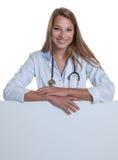 Doctor de sexo femenino caucásico joven detrás de un tablero en blanco Imágenes de archivo libres de regalías