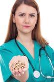 Doctor de sexo femenino con el estetoscopio que sostiene pils en su mano imagen de archivo