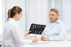 Doctor de sexo femenino con el viejo hombre que mira la radiografía Imagen de archivo libre de regalías