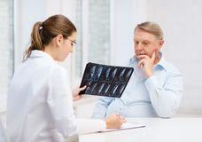 Doctor de sexo femenino con el viejo hombre que mira la radiografía Fotos de archivo