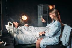 Doctor de sexo femenino con la jeringuilla contra el paciente masculino foto de archivo libre de regalías