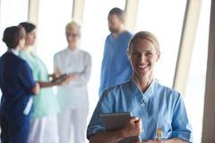 Doctor de sexo femenino con la tableta que se coloca delante del equipo Imagenes de archivo