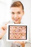 Doctor de sexo femenino con PC y sonrisas de la tableta Imagen de archivo libre de regalías