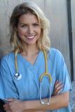 Doctor de sexo femenino confiado que presenta en su oficina y que sonríe en el concepto de la cámara, de la atención sanitaria y  foto de archivo libre de regalías