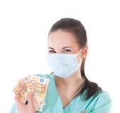Doctor de sexo femenino del cirujano que sostiene el dinero Imagen de archivo